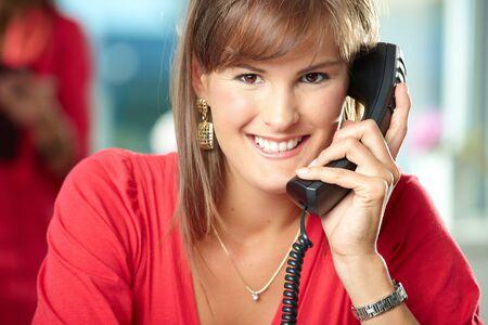 business administration: Primer retrato de joven empresaria hablando por tel�fono de l�nea fija, sonriendo.