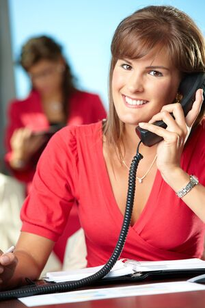 Young businesswoman sitting at desk in office, talking on landline phone, smiling. Stock Photo - 7628614