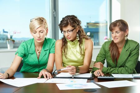 Three attractive businesswomen sitting at meeting room, discussing financial charts on table. photo
