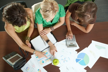 Young businesswomen sitting at table in meeting room, discussing finacial charts. Overhead shot. photo