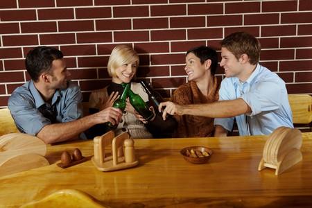 socializando: Amigos que se divierten en el bar, sentados juntos a la mesa, teniendo la cerveza, riendo.