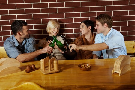 Friends having fun at bar, sitting together at table, having beer, laughing. Stock Photo - 7628849