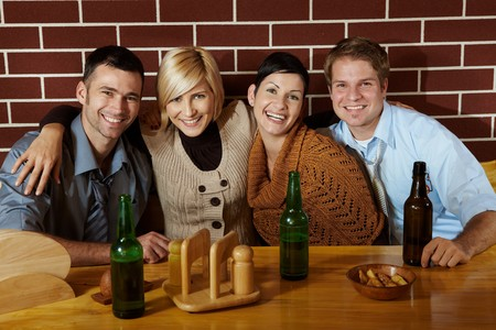 Portrait of friends in pub, sitting at table, smiling at camera. Stock Photo - 7628852