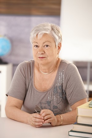 Portrait of senior teacher sitting at desk in classroom, looking at camera. photo