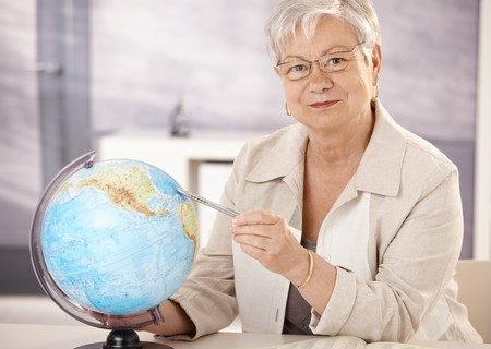Senior teacher sitting at desk, pointing at globe, teaching geography in elementary school. Stock Photo - 7639245