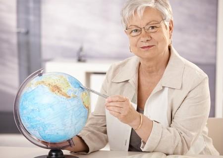 Senior teacher sitting at desk, pointing at globe, teaching geography in elementary school. photo