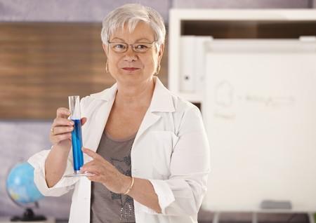 Senior teacher standing in classroom, holding test tube, teaching chemistry in elementary school. photo