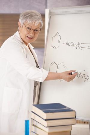 Senior teaching chemistry in school, explaining molecular formulas on whiteboard. photo