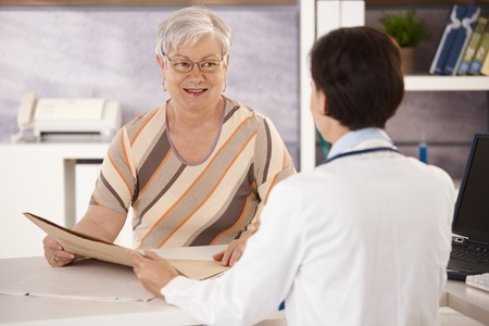 prestar atencion: Pensionista femenina en Oficina de médicos escuchando a la explicación de los médicos.