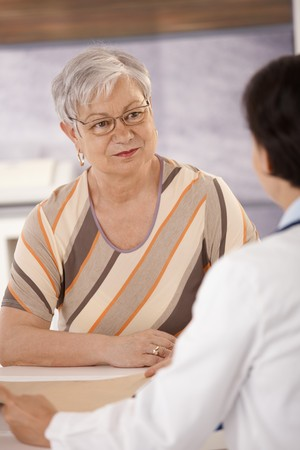 Female pensioner at doctors office listening to doctors explanation. photo