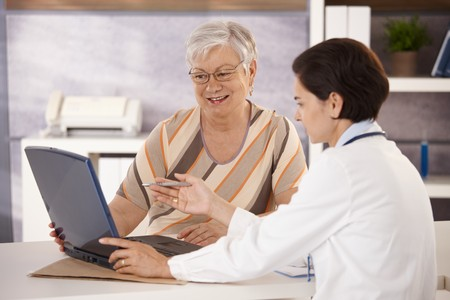 explaining: Doctor explaining results to senior patient in office, using laptop computer.