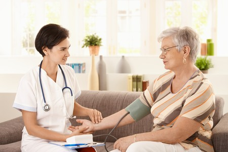 old people in care: Female doctor measuring blood pressure of senior woman at home.