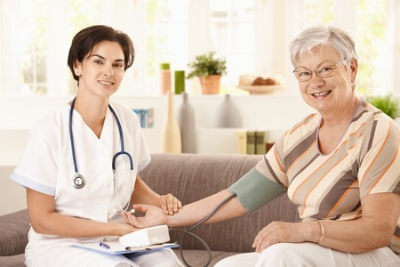 home health care: Nurse measuring blood pressure of senior woman at home. Looking at camera, smiling.