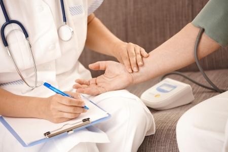 enfermera con paciente: Detalle de la enfermera, medir la presión arterial y comprobando el latido del corazón en de muñeca la mujer senior.  Foto de archivo