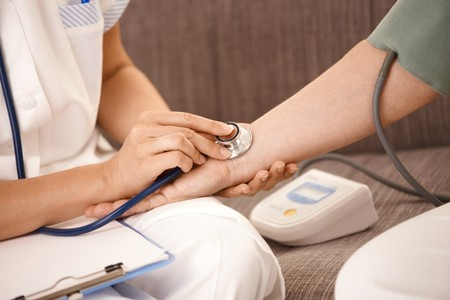 age test: Closeup of nurse using stethoscope on wrist of senior woman.