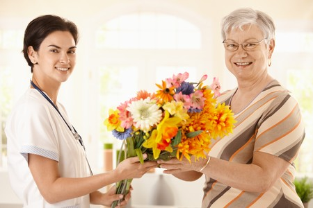 Senior patient giving flowers to nurse. Looking at camera, smiling. Stock Photo - 7639237