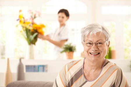 home health care: Portrait of happy elderly woman sitting on sofa at home, nurse arranging flowers in background.