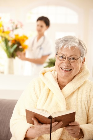 heal care: Portrait of happy elderly woman sitting on couch, reading book, nurse arranging flowers in background. Stock Photo