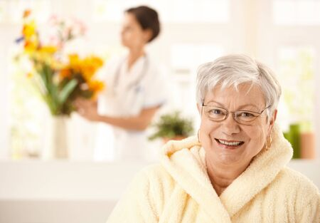 home care nurse: Portrait of happy elderly woman wearing bathrobe, nurse arranging flowers in background.