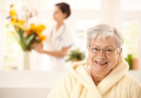 age care: Portrait of happy elderly woman wearing bathrobe, nurse arranging flowers in background.