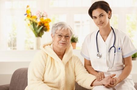Nurse measuring pulse rate of senior woman at home. Looking at camera, smiling. Stock Photo - 7639174