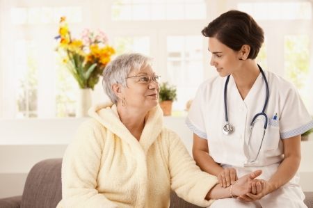 heal care: Nurse measuring heartbeat of senior woman at home. Looking at camera, smiling. Stock Photo