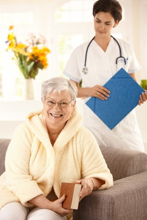 Happy elderly woman sitting on sofa at home, nurse watching from behind. photo