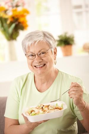 Happy senior woman eating healthy salad at home. Looking at\ camera, smiling.