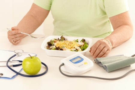 diabetic: Elderly woman eating healthy diet, salad and apple.