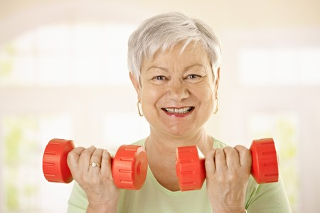 Closeup portrait of active senior woman doing dumbbell exercises at home, smiling. photo