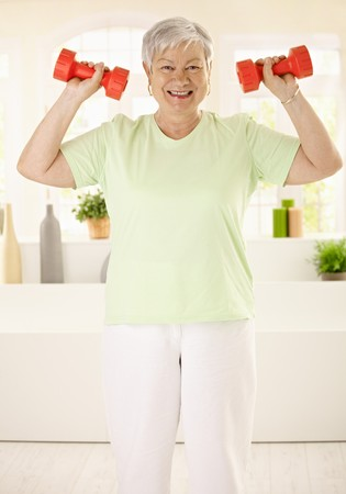 Energetic elderly woman doing dumbbell exercises at home, smiling. photo