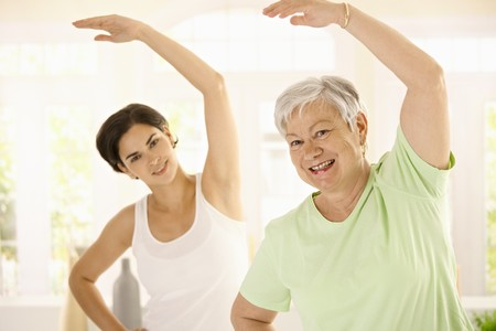 home trainer: Healthy elderly woman doing exercises with personal trainer at home, smiling. Stock Photo