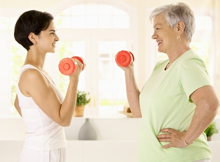 home trainer: Healthy elderly woman doing dumbbell exercise with personal trainer at home, smiling. Stock Photo