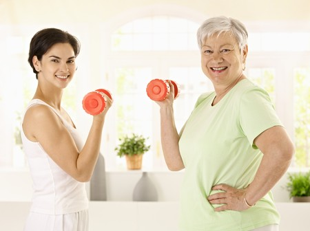 Healthy senior woman doing dumbbell exercise with personal trainer at home, smiling. photo