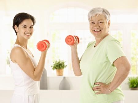 haciendo ejercicio: Mujer senior saludable haciendo ejercicios de pesas con entrenador personal en casa, sonriendo.