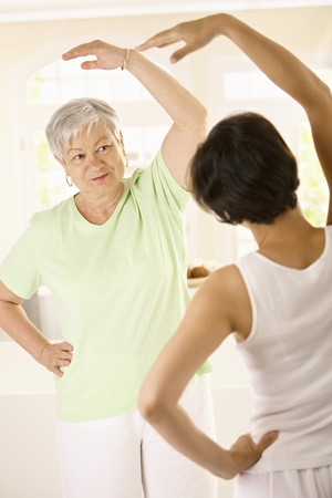 home trainer: Healthy senior woman doing exercises with personal trainer at home, smiling.