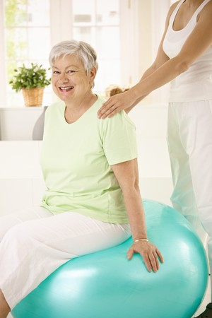 Personal trainer assisting senior woman doing fit ball exercise at home, smiling. photo