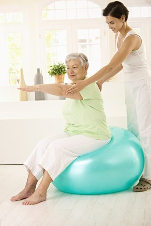 home trainer: Personal trainer assisting senior woman doing fit ball exercise at home, smiling.