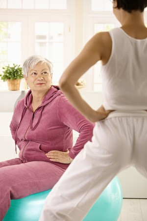 boomers: Elderly woman sitting on fit ball looking at personal trainer demonstrating exercise. Stock Photo