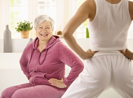 demonstrated: Senior woman doing exercises demonstrated by personal trainer, looking at camera, smiling.