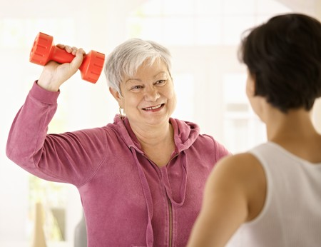 Senior woman doing dumbbell exercise with personal trainer at home, smiling. photo
