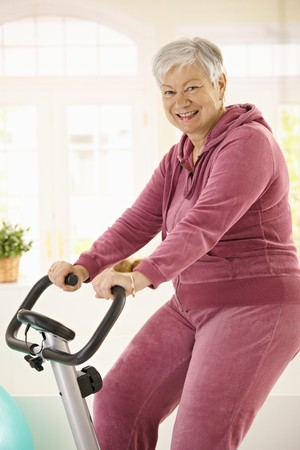 stationary bicycle: Healthy elderly woman training at home with exercise bike, smiling. Stock Photo