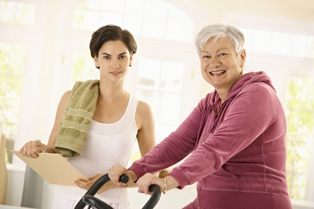 home trainer: Healthy elderly woman training at home with exercise bike, assisted by personal trainer.