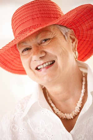 only mature women: Closeup portrait of happy senior woman wearing hat, looking at camera, smiling.