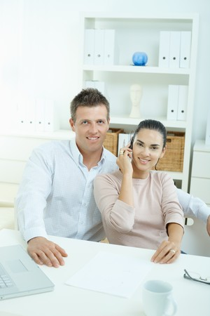 sinecure: Couple working on laptop computer at home office, happy, smiling. Woman calling on mobile phone. Stock Photo