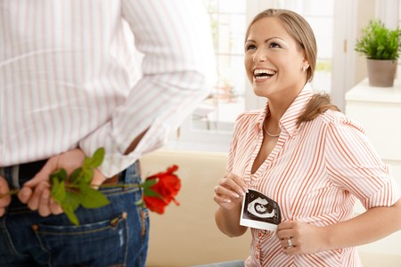 Laughing pregnant woman with ultrasound baby picture in hand getting red rose from man. photo