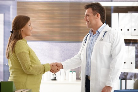 color consultant: Smiling doctor shaking hands with pregnant woman in consulting room.
