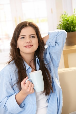 Attractive girl sitting on couch holding coffee mug, smiling. photo