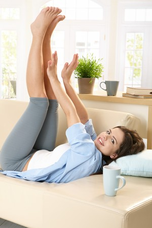 Cheerful girl looking at camera, lying on sunlit living room couch, stretching arms and legs. Stock Photo - 7723741