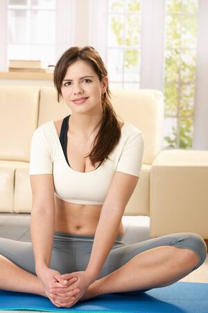 Portrait of girl wearing gym suit sitting on blue floor mat, smiling at camera in living room. Stock Photo - 7723755